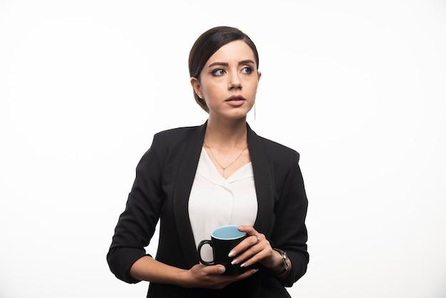 Una donna in abito con una tazza di caffè in mano sul muro bianco.