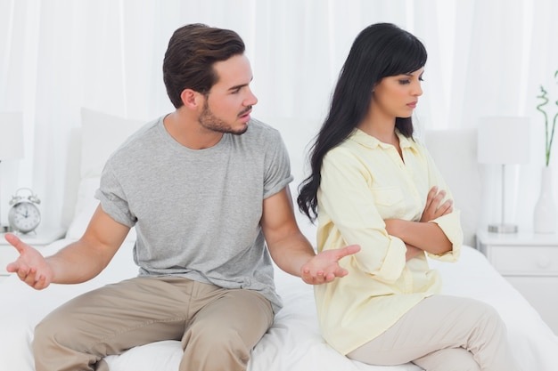 Woman sulking while her boyfriend is explaining himself