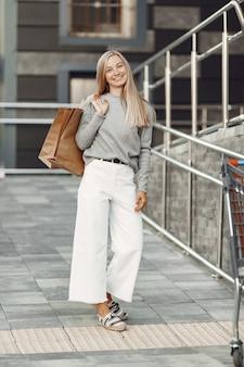 Donna in una città estiva. signora con borse marroni. donna in un maglione grigio.