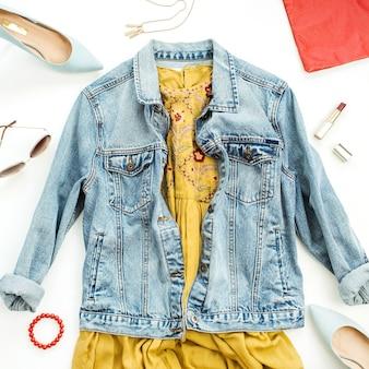 女性の夏のカラフルなファッションの服やアクセサリーを白い表面に設定します。