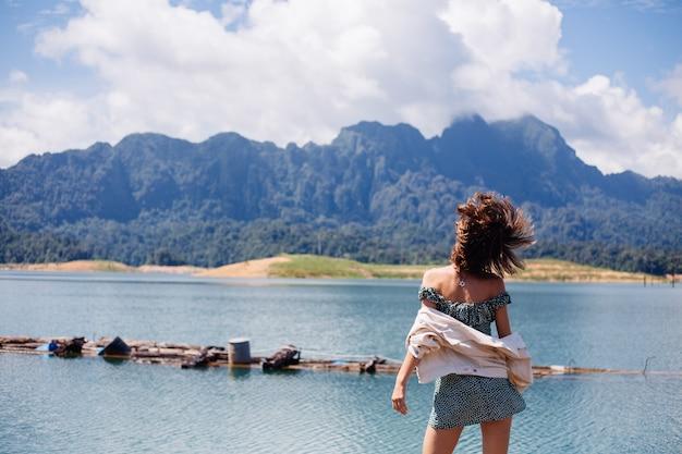 Donna in abito estivo e giacca turistica viaggia in thailandia, parco nazionale di khao sok, splendida vista sulle barche e sul lago.