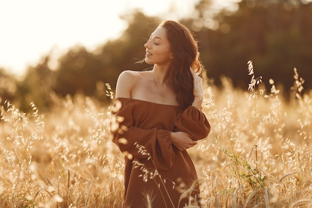 Woman in a summer field. brunette in a brown sweater.