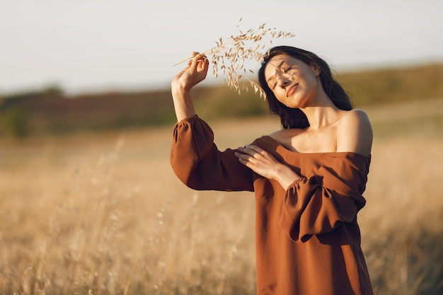 Woman in a summer field. brunette in a brown sweater.