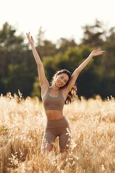 Woman in a summer field. brunette in a spots suit.