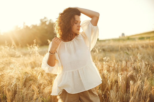 Woman in a summer field. brunette in a white shirt.