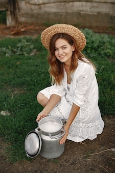 Woman in a summer field. girl in a white dress. woman with barrel of milk.