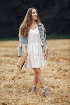 Woman in a summer field. lady in a white dress.