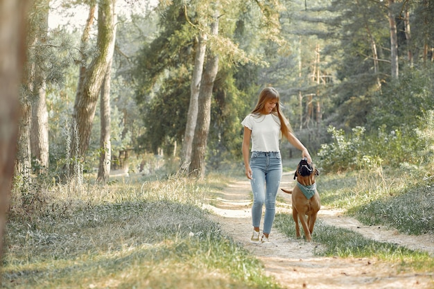 Woman in a summer forest playing with dog