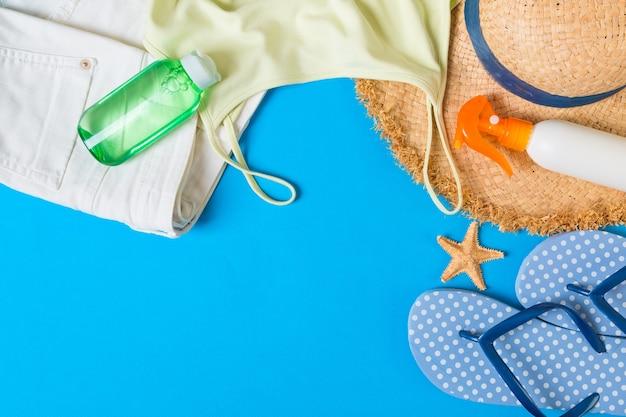 青い背景の上の女性の夏の服の上面図。ファッション休暇のコンセプト。