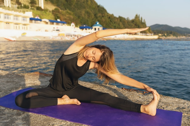 Woman on a summer sunny evening on a pier near the sea performs a muscle stretching exercise