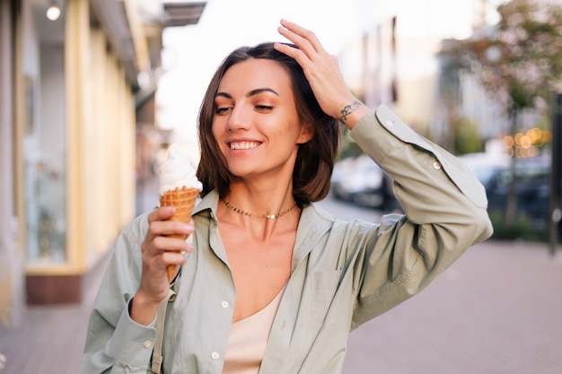 Woman at summer sunset time having ice cream cone at city street