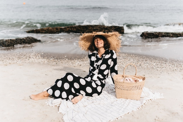 Woman in summer vacation wearing straw hat and beach dress enjoying the view at the sea