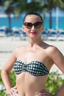 セクシーな海のブラジャービキニトップで女性の日光浴。太陽が降り注ぐビーチでサングラスをかけた官能的な女の子。夏休み、リラックス。ワンダーラスト、旅行、冒険、発見