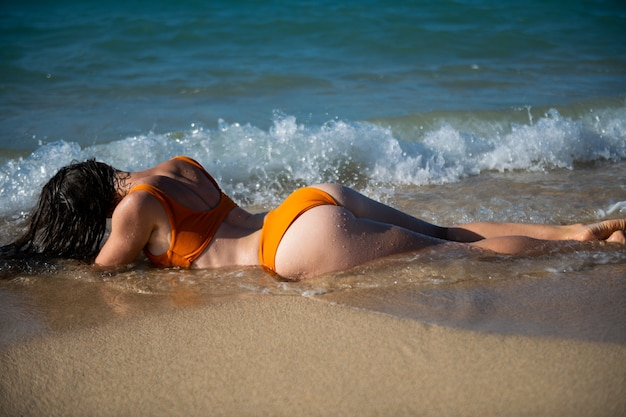 Woman sunbathes on the beach of the island on summer vacation. beautiful ass and buttocks.