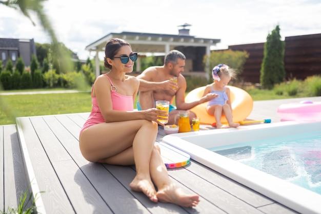 Женщина загорает. красивая стройная женщина в розовом купальнике, загорающая рядом с мужем и дочерью