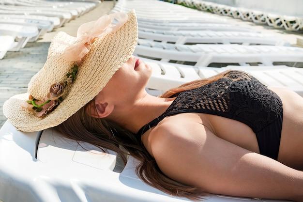 熱帯旅行リゾートでビキニで日光浴をしている女性。プールの近くのサンラウンジャーに横たわって笑っている美しい若いアジアの白人女性。眠っている籐の麦わら帽子の下で女性のクローズアップ。