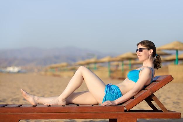 Woman sunbathing on wooden lounger