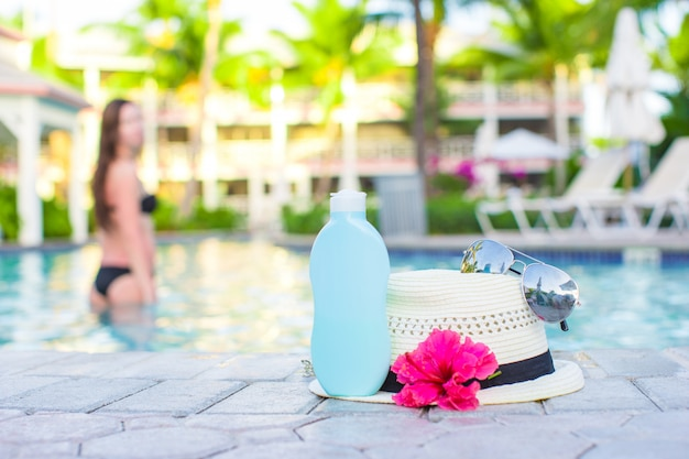 Woman, suncream, hat, sunglasses, flower and tower near swimming pool