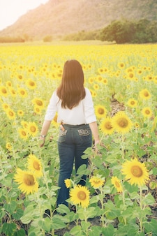 Woman in sunflower field. healthy food product.