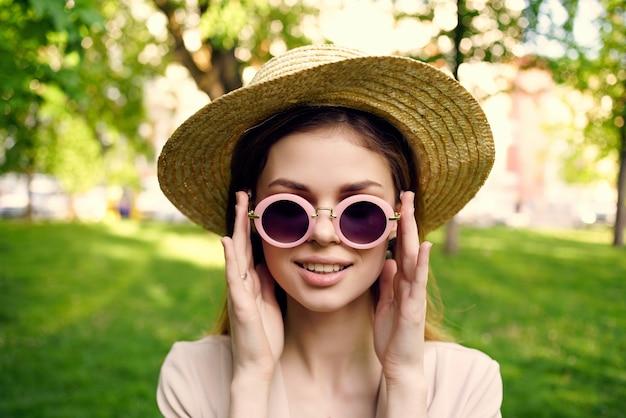 公園の緑の草モデルの女性のサングラスと帽子