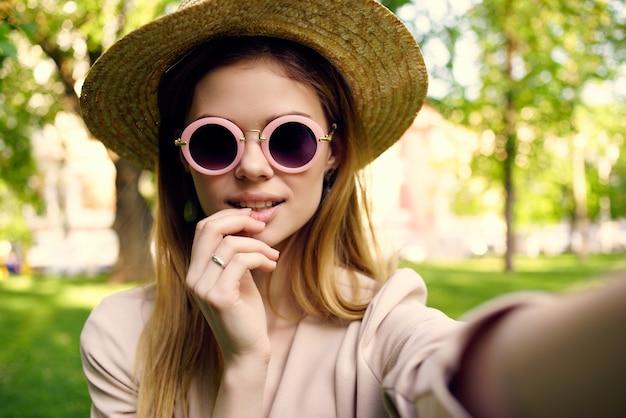 公園の緑の芝生で女性のサングラスと帽子
