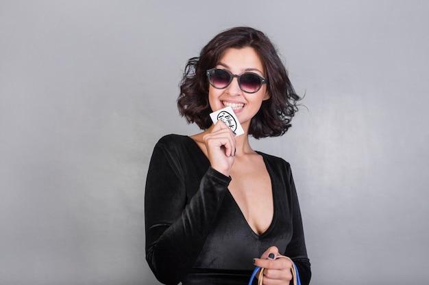 Woman in sunglasses biting credit card
