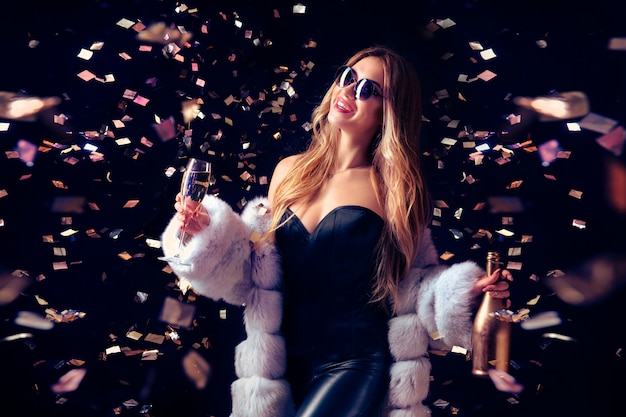 Woman in sunglasses celebrating with champagne