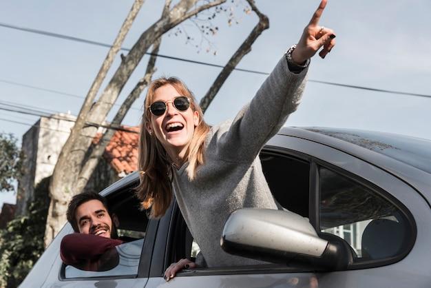 Donna in occhiali da sole appesa fuori dal finestrino della macchina