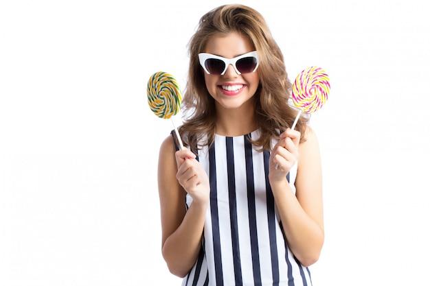 Woman in sunglasses holding lollipop.