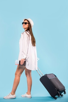Woman in sunglasses and panama standing and holding suitcase