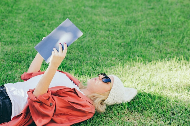 Woman in sunglasses reading book on lawn
