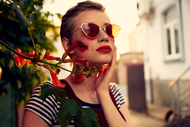 Woman in sunglasses on the street near flowers posing lifestyle