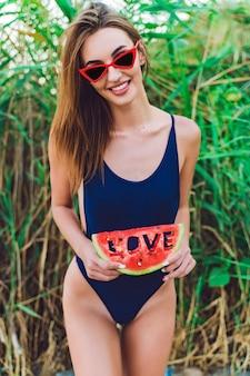 Woman in sunglasses and swimwear hold slice of watermelon