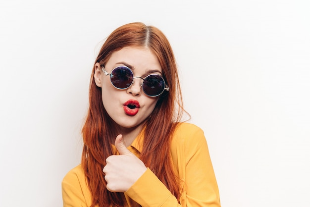 Woman in sunglasses, white wall, joy and surprise