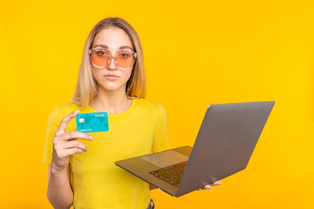 Woman in sunglasses with laptop computer while holding credit card and looking at the camera over yellow.