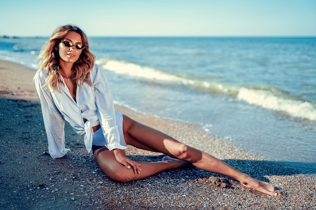 Woman in sunglasses with long hair in swimsuit and white t-shirt lying on summer beach