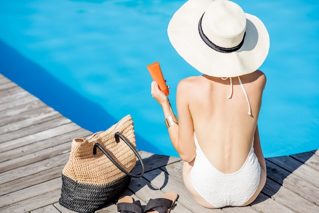 Woman in sunhat sitting with sunscreen lotion near the basin with blue water. sunscreen solar cream uv protection concept