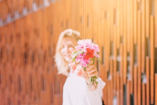 Woman in sunlight showing flowers toward camera