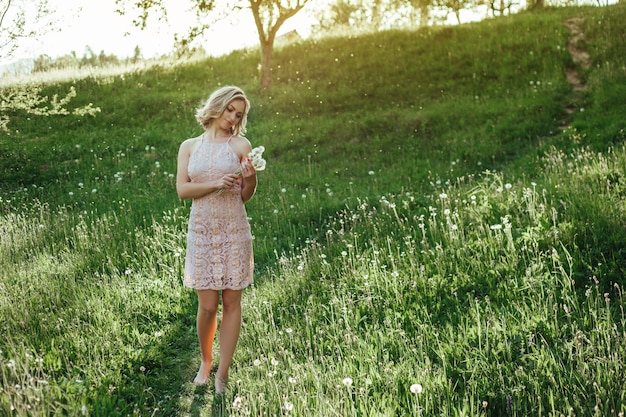 A woman at sunset in a field of dandelions in a pink dress . the concept is not allergic .