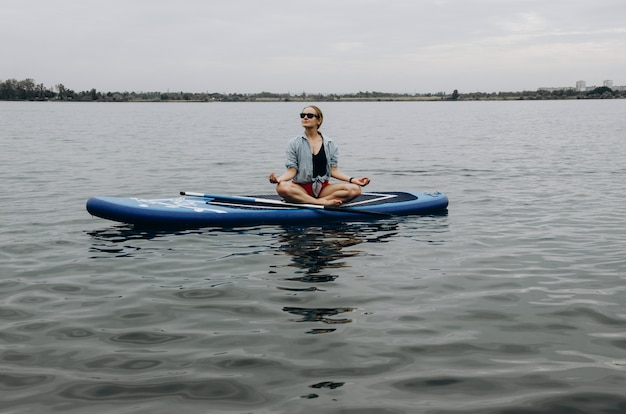 Woman on sup board. a beautiful young woman relaxes on a sup board. standup paddleboarding