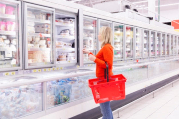 A woman in a supermarket in the frozen food section selects a product.