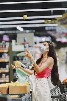 Woman in a supermarket. lady in a respirator. girl makes parchases.