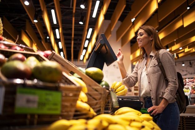 Donna al supermercato utilizzando la bilancia digitale self-service per misurare il peso della frutta