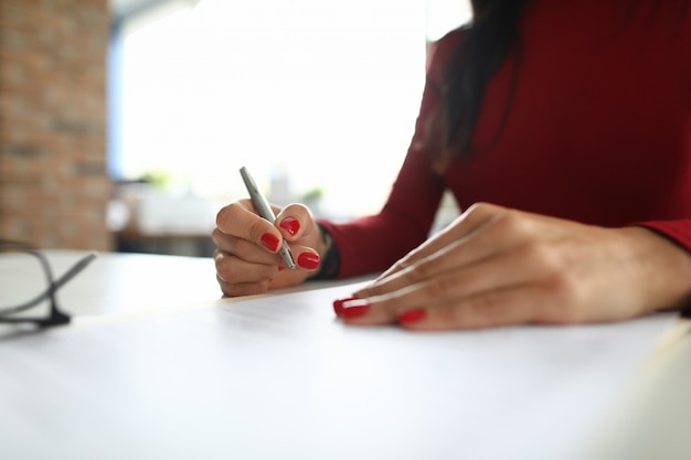Woman supervisor makes notes at the table