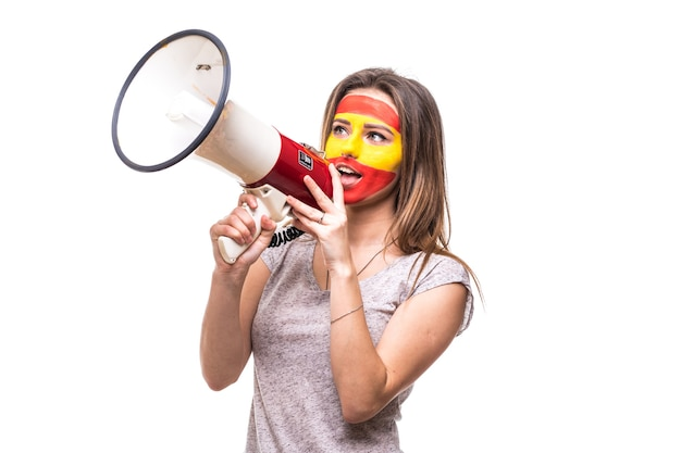 Woman supporter loyal fan of spain national team painted flag face get happy victory screaming into megaphone with pointed hand. fans emotions.