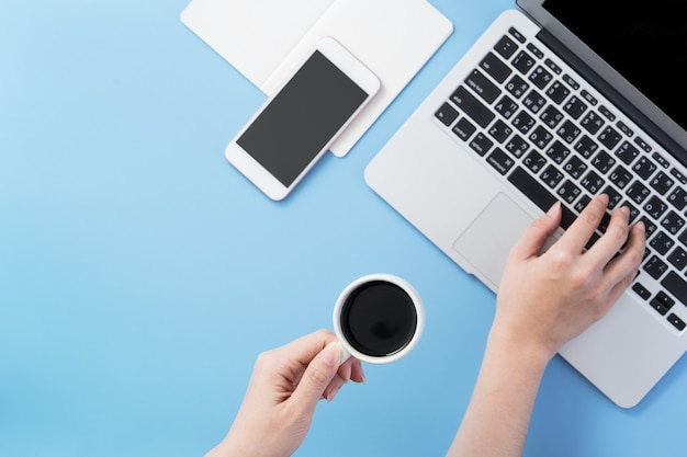 Woman surf internet for job hunting. freelancer blog writer typing on a cleam light blue desk with coffee, copy space, flat lay, top view, mock up