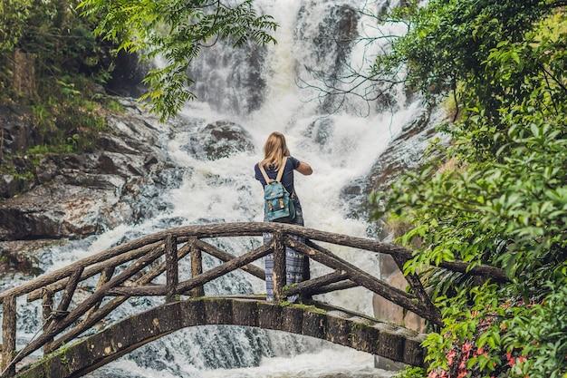 Woman in the surface of beautiful cascading datanla waterfall in the mountain town dalat, vietnam
