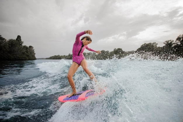 Woman surfer riding down the blue splashing river against sky