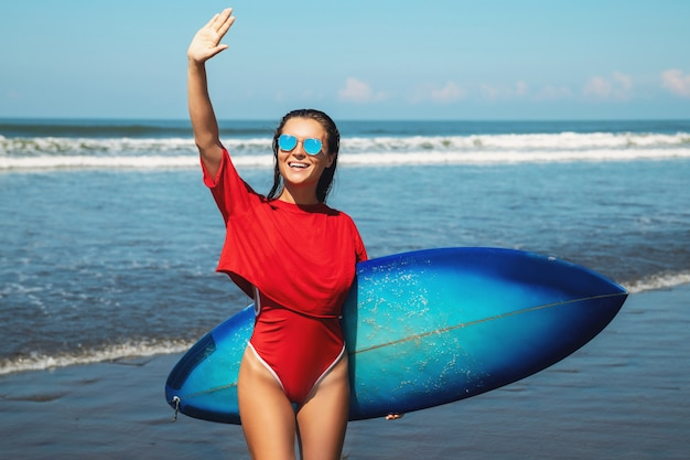 Женщина-серфер с доской на пляже