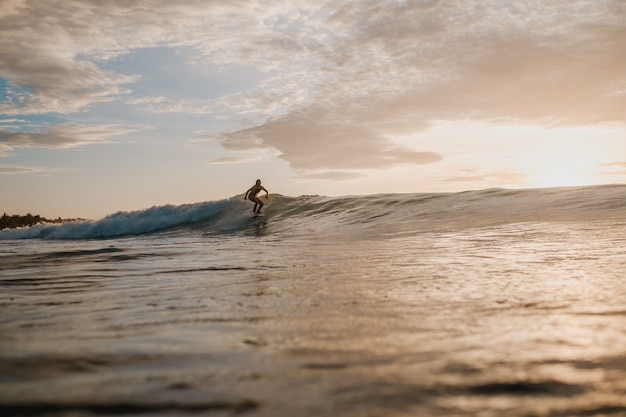 Woman surfing in the mentawai islands, sumatra, indonesia